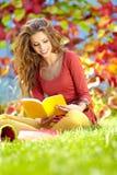 Молодая девушка брюнет читая книгу Стоковые Фото