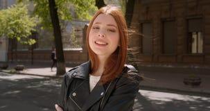 Молодая девушка имбиря в кожаной куртке усмехаясь мило в камеру и исправляя ее волосы на активной предпосылке улицы города сток-видео