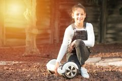 Молодая девушка подростка хипстера балансируя на электрическом завишет доска, собственная личность двойного колеса балансируя пар стоковое фото