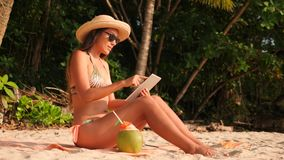 Молодая девушка смешанной гонки привлекательная в бикини загорая на тропическом песчаном пляже рая и используя передвижное устрой видеоматериал