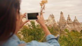 Молодая девушка смешанной гонки туристская фотографируя красивые утесы горы используя мобильный телефон в Cappadocia, Турции 4K S акции видеоматериалы