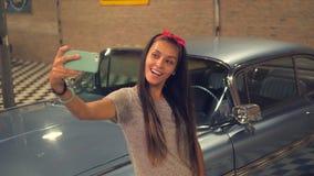 Молодая девушка смешанной гонки pin-вверх Hipser принимая Selfie с мобильным телефоном на винтажный гараж и старый автомобиль 4K, сток-видео
