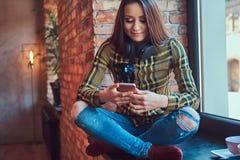 Молодая девушка студента брюнет в музыке вскользь одежд слушая пока использующ smartphone пока сидящ на силле окна внутри Стоковые Изображения