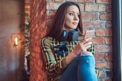 Молодая девушка студента брюнет в музыке вскользь одежд слушая пока использующ smartphone пока сидящ на силле окна внутри Стоковое Изображение