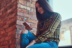 Молодая девушка студента брюнет в музыке вскользь одежд слушая пока использующ smartphone пока сидящ на силле окна внутри Стоковая Фотография