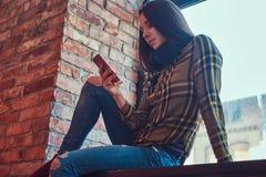Молодая девушка студента брюнет в музыке вскользь одежд слушая пока использующ smartphone пока сидящ на силле окна внутри Стоковое Изображение RF