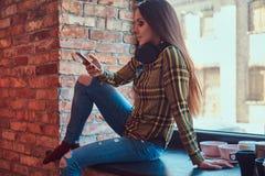Молодая девушка студента брюнет в музыке вскользь одежд слушая пока использующ smartphone пока сидящ на силле окна внутри Стоковое Фото