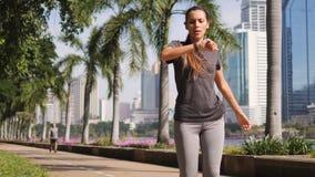 Молодая девушка фитнеса спорта смешанной гонки бежать в парке города и используя умное устройство вахты отслежывателя фитнеса для сток-видео