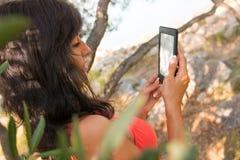Молодая девушка читая EBook брюнет на парке Стоковые Изображения