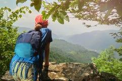 Молодая девушка hiker наслаждаясь красивым видом от высокой скалы в армянских горах в лете стоковые изображения rf