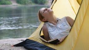 Молодая девушка hiker читает книгу в располагаясь лагерем шатре, мечтах и взглядах вокруг Счастливый усмехаться Здоровая активная акции видеоматериалы