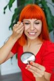 Молодая девушка redhead используя щипчики Стоковые Фото