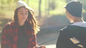 Молодая девушка skateborder ехать скейтборд к парню и давать высоко--5 движение медленное Хобби и образ жизни сток-видео