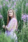 Молодая длинн-с волосами девушка в зацветая поле Иван-чая с букетом цветков стоковые изображения rf