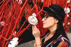 Молодая длинн-с волосами женщина брюнета в ярком платье против красной стены стоковые фото