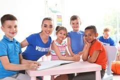 Молодая добровольная книга чтения с детьми на таблице стоковые фотографии rf