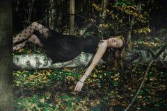 Молодая добросердечная ведьма в черном платье с черной маской в мистическом лесе в различных представлениях Обрабатывать искусств стоковое изображение