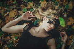 Молодая добросердечная ведьма в черном платье с черной маской в мистическом лесе в различных представлениях Обрабатывать искусств стоковая фотография