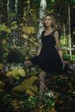 Молодая добросердечная ведьма в черном платье с черной маской в мистическом лесе в различных представлениях Обрабатывать искусств стоковые фотографии rf