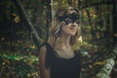 Молодая добросердечная ведьма в черном платье с черной маской в мистическом лесе в различных представлениях Обрабатывать искусств стоковая фотография rf
