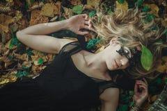 Молодая добросердечная ведьма в черном платье с черной маской в мистическом лесе в различных представлениях Обрабатывать искусств стоковое изображение rf