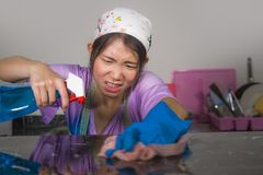 Молодая довольно перегружанная и усиленная азиатская корейская женщина горничной обслуживания работая отечественные чистка и стир стоковая фотография rf