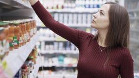 Молодая домохозяйка выбирает законсервированные грибы в магазине видеоматериал