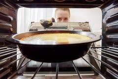 Молодая домохозяйка смотря чизкейк в печь в кухне стоковое фото
