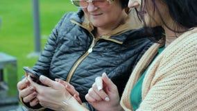 Молодая дочь учащ ее матери как использовать smartphone 2 брюнет различных времен сидят на стенде сток-видео