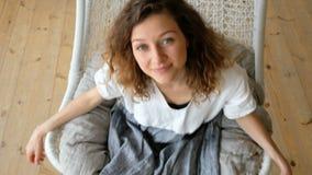 Молодая европейская девушка в linen платье отбрасывает в гамак-качании в квартире просторной квартиры и смотрит прямо в камеру видеоматериал