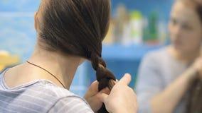 Молодая европейская женщина заплетает оплетку на зеркале сток-видео