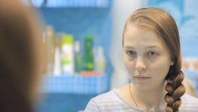 Молодая европейская женщина заплетает оплетку на зеркале акции видеоматериалы