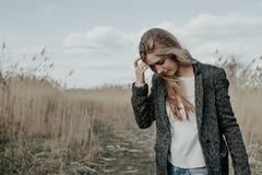 Молодая европейская женщина идя на проселочную дорогу через bulrush Стоковое Изображение RF
