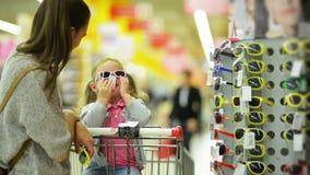 Молодая жена в вскользь одежде выбирая солнечные очки для ее маленькой дочери стоя близко полка супермаркета акции видеоматериалы