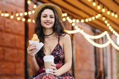 Молодая женская модель с темными глазами, красный цвет покрасила губы нося платье и шляпу лета держа в coffe рук на вынос и круас стоковые изображения