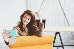молодая женственная женщина блоггера делая selfie или онлайн широковещание на социальных средствах массовой информации одних Стоковые Фото
