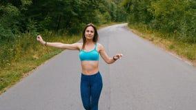 Молодая женщина атлетики идя на дорогу в фитнесе outdoors леса съемка с steadicam акции видеоматериалы
