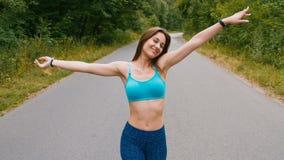Молодая женщина атлетики идя на дорогу в фитнесе outdoors леса съемка с steadicam видеоматериал