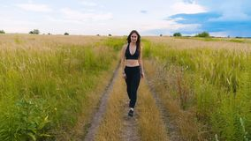 Молодая женщина атлетики идя на проселочную дорогу в красивом поле фитнес outdoors съемка с steadicam акции видеоматериалы