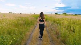 Молодая женщина атлетики идя на проселочную дорогу в красивом поле фитнес outdoors съемка с steadicam видеоматериал