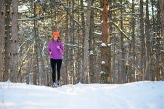 Молодая женщина бежать в красивом лесе зимы на солнечном морозном дне Активная принципиальная схема уклада жизни Стоковые Изображения RF