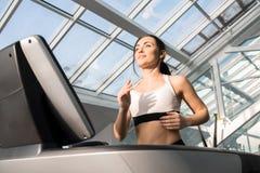Молодая женщина бежать на третбане в спортзале стоковое изображение