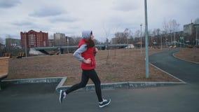 Молодая женщина бежит в парке на пасмурный день акции видеоматериалы