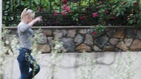 Молодая женщина бежит и подпрыгивает joyfully вдоль изгороди сток-видео
