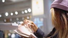 Молодая женщина битника выбирает новые тапки в магазине Шоппинг сток-видео