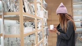 Молодая женщина битника в стеклах моды выбирает домашние acessories в магазине Шоппинг сток-видео