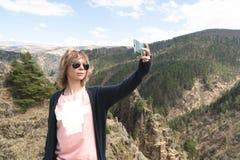 Молодая женщина битника делает selfie на верхней части ландшафта горной цепи скалы изумительного Битник adventurousness Путешеств стоковое изображение