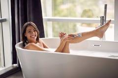 Молодая женщина брея ее ноги в ванне с пеной стоковые фотографии rf