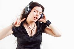Молодая женщина брюнета в больших наушниках слушая музыку и имея потеху стоковое фото