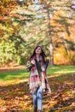 Молодая женщина брюнета в парке окруженном листьями падения стоковое изображение rf